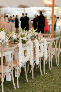 Floral leis draped over bride and groom chairs