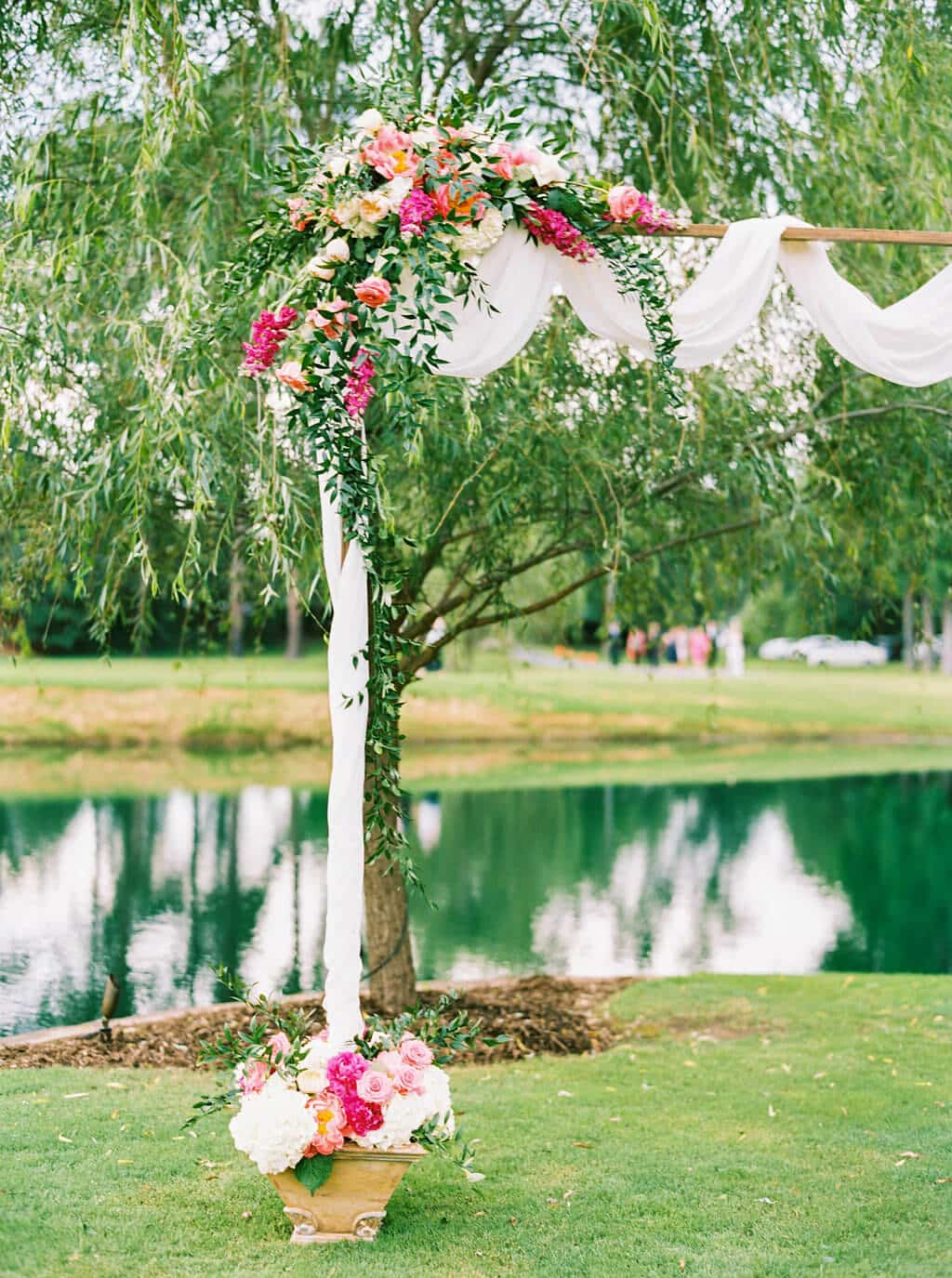 Wedding ceremony arbor with hot pinks, peaches, and greenery