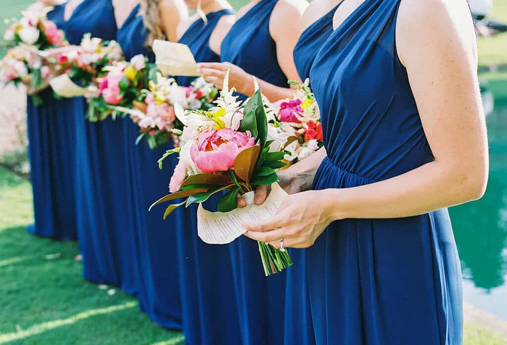 Bridesmaids in blue dresses holding bouquets with coral charm peonies